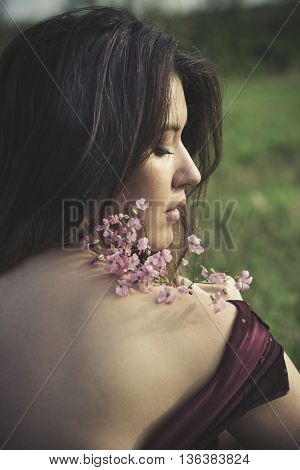 summer young woman portrait with flower on field