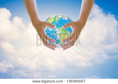 Human hands on both sides holding the world sky in the background blurred.Environment Day concept. Ecology concept.Environment Day concept. Ecology concept..Elements of this image furnished by NASA.