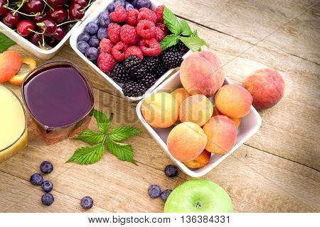 Organic fruits and fresh juices on rustic wooden table