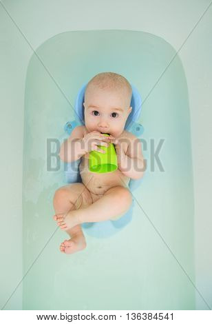 Cute baby swimming in bathroom and playing with toy.