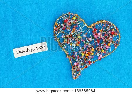 Dank je wel (thank you in Dutch) card with heart made of colorful beads on blue background