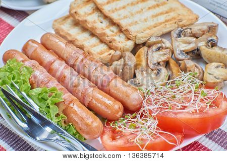 Fried sausages wrapped in bacon on a plate