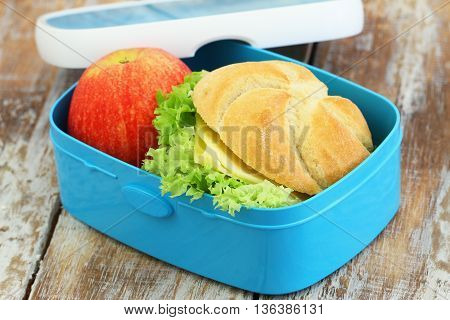 School lunch box with crunchy roll with cheese and lettuce, and red apple