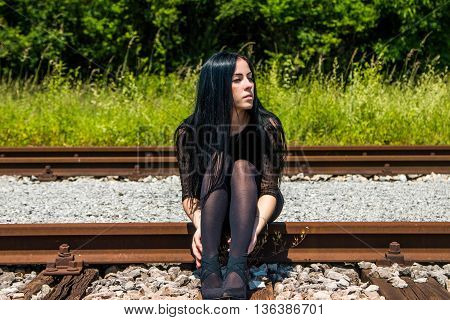 Young beautiful girl in black dress and nylons sitting on rail tracks and daydreaming, green grass and trees in background