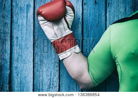 Man's hand in a boxing glove on a blue background