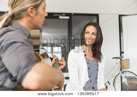 Young man playing guitar and attractive woman enjoying it
