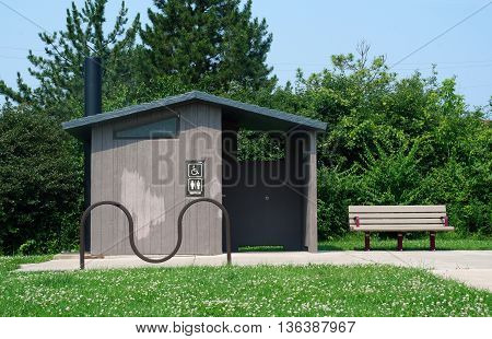 JOLIET, ILLINOIS / UNITED STATES - JUNE 30, 2015: An outhouse is available for visitors to the Forest Preserve District of Will County's Joliet Iron Works Historic Site.