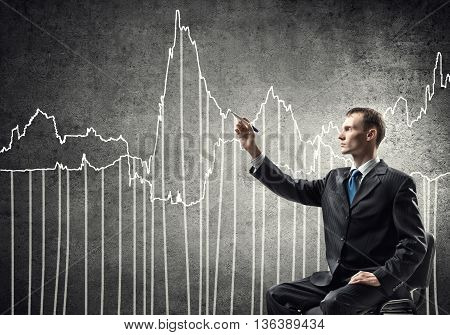 Young businessman sitting in chair and drawing growth dynamics concept