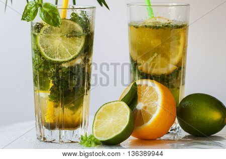 Refreshing summer cocktail mojito with green basil, lemon, lime and ice on a light background
