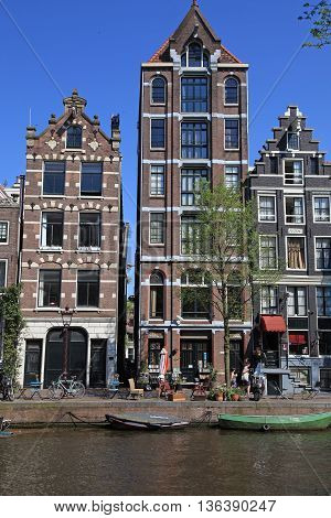 AMSTERDAM, NETHERLANDS - MAY 8, 2016: View of Amsterdam canals and typical dutch houses Amsterdam, Holland, Netherlands. Vertical image