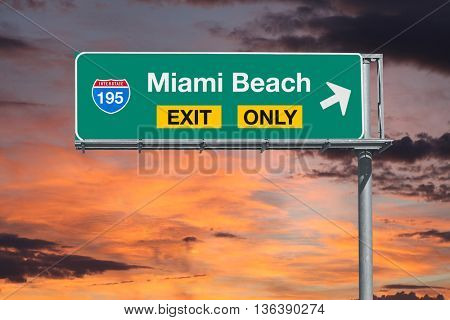 Miami Beach exit only highway sign with sunrise sky.