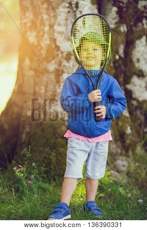 Little boy playing tennis at park in the forest