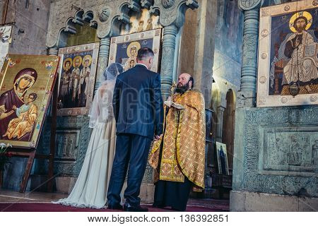 Mtskheta Georgia - April 26 2015. Orthodox priest gives blessing couple after wedding ceremony in Svetitskhoveli Cathedral (english - Cathedral of the Living Pillar) in Mtskheta one of the oldest cities of Georgia