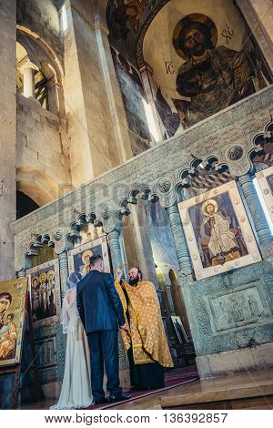 Mtskheta Georgia - April 26 2015. Orthodox priest blesses the bride and groom after the wedding ceremony in Svetitskhoveli Cathedral (english - Cathedral of the Living Pillar) in Mtskheta one of the oldest cities of Georgia