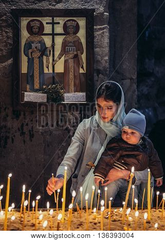 Mtskheta Georgia - April 26 2015. Young woman with his baby son lights offering candle in the Holy Cross Monastery of Jvari near Mtskheta one of the oldest cities of Georgia