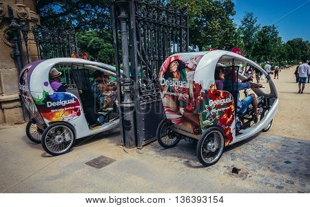 Barcelona Spain - May 23 2015. Cycle taxi for tourists passes entry gate of Citadel Park in Barcelona