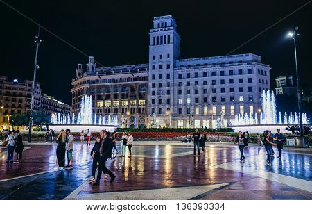 Barcelona Spain - May 23 2015. People walks at Catalonia Square. View with buildings of Public Library of Barcelona and Banco Espanol de Credito on background