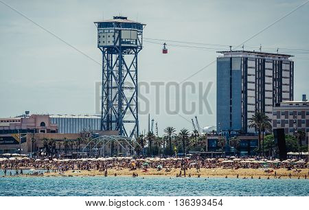 Barcelona Spain - May 24 2015. View of Torre Sant Sebastia of Port Vell Aerial Tramway. La Barceloneta beach on foreground
