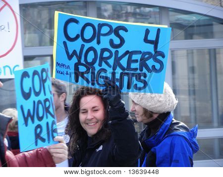 "Lady police office holding ""Cops 4 Workers Rights"" sign"