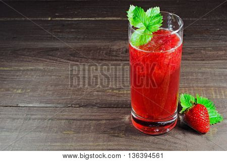 strawberry and juice with pulp in the glass with green leaf on wooden background. summer drink