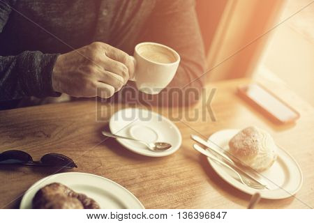 Coffee time. Man drinking cappuccino in morning cafe, image toned.