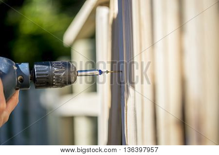 Person building a wooden fence with a drill and screw using a hand held power drill in a concept of yard maintenance renovations and DIY.