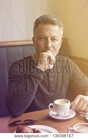 Attractive mid adult man drinking morning coffee in cafe, image toned.