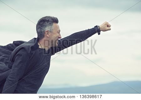 Superhero flying over sky and mountain landscape over sunrise. Success, power
