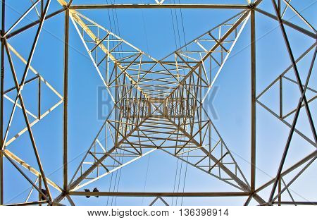 High section of electric power line tower structure against blue sky