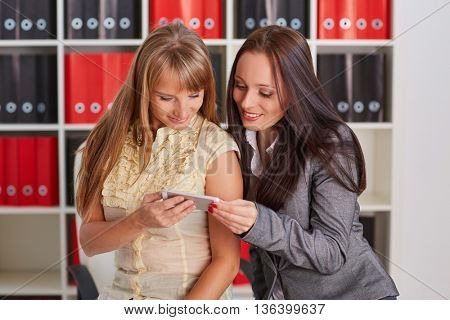 Two young business women with mobile phone in the office.