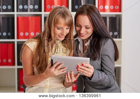 Two young business women with computer tablet in the office.