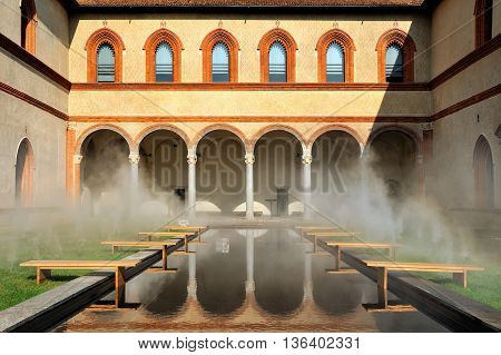 Middle Ages courtyard with pool in surreal fog