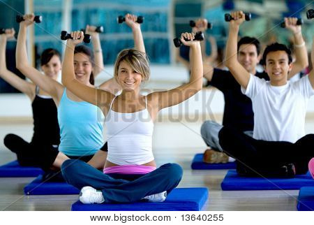 Group of people exercising at the gym with freeweights