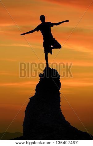 Man balancing on top of mountain risk taking and challenge concept