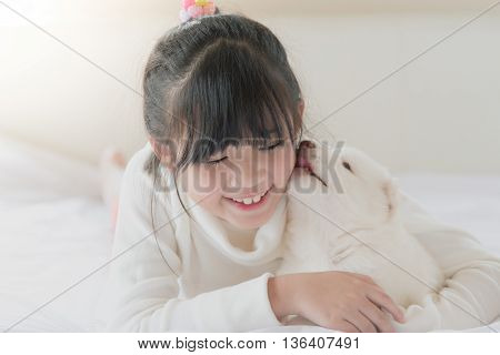 White puppy is lovingly licking the cheek of a asian girl.