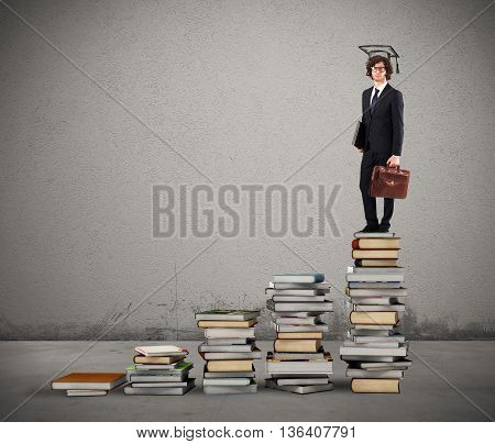 Scale with books and man with graduation hat
