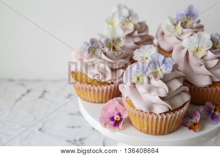 Purple Cupcakes With Sugared Edible Flowers On Cake Stand Copy Space Background.