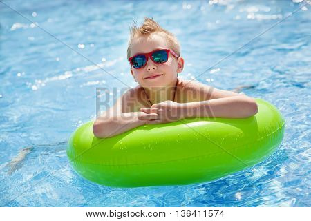 Little boy swimming in the pool with big bright green rubber ring, having fun in aquapark.