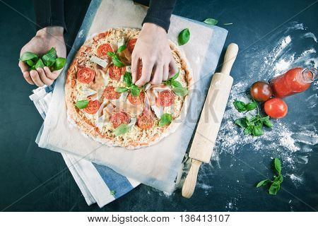 Hands of baker adding ingredients into pizza during pizza preparation at kitchen