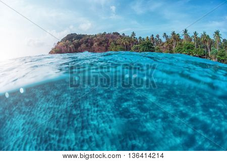Split underwater shoot of a sandy sea bottom and green tropical island with cloudy sky above sea surface