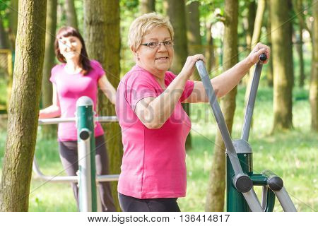 Senior And Young Woman Exercising Upper Body On Outdoor Gym, Healthy Lifestyle