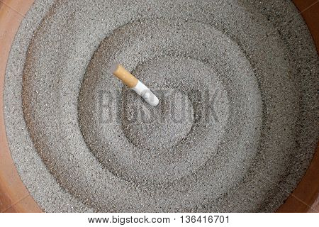 photo of smoked cigarettes in sand ashtray