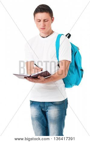 Portrait of a caucasian guy carrying some books and a backpack, isolated on white background. Smart  student of college or university writes in a notebook lecture.