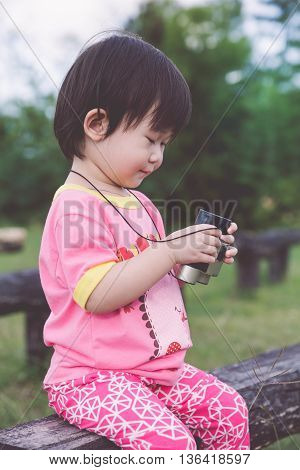 Happy asian girl with telescope on blurred nature background. Child playing outdoors in the day time travel on vacation.