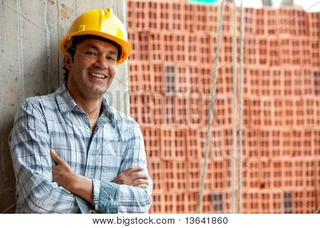 Happy male construction worker wearing a helmet and smiling