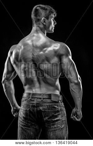 Muscular bodybuilder guy doing posing over black background. He turned his back. Black and white, b w
