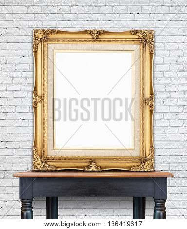 Blank vintage golden photo frame lean at white brick wall on wood tableTemplate Mockup for add picture.