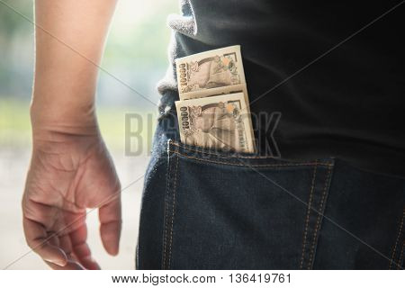 Close Up of Man Wearing Jeans with Japanese banknote in Back Pocket