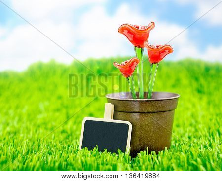 Red Flower Made Of Glass In Brown Flowerpot And Blackboard On Green Grass With Blue Sky,spring Seaso