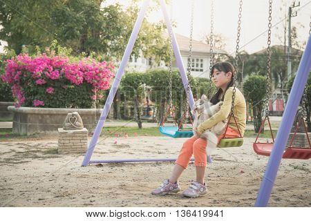 Asian girl and siberian husky puppy sitting on chain swing in the park